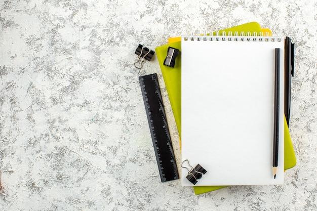 Vista superior do caderno espiral fechado branco e suprimentos de escritório no lado esquerdo em fundo branco