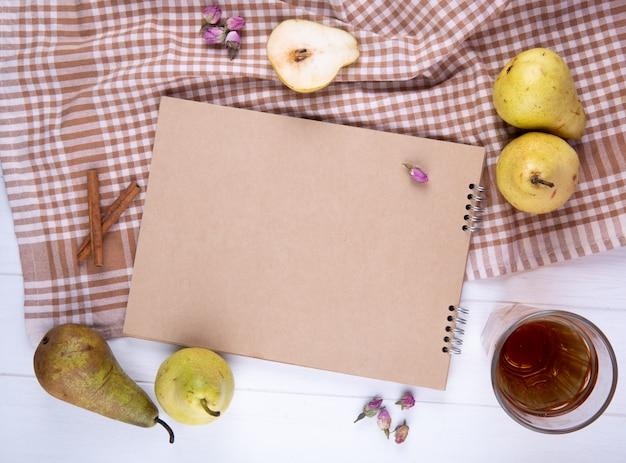 Vista superior do caderno feito de papel ofício com peras frescas maduras e um copo de limonada na toalha de mesa xadrez