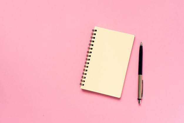 Vista superior do caderno vazio com caneta no conceito de fundo de cor rosa