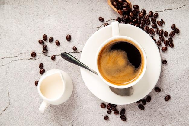 Vista superior do café americano feito em um copo branco com leite em uma jarra no fundo de concreto