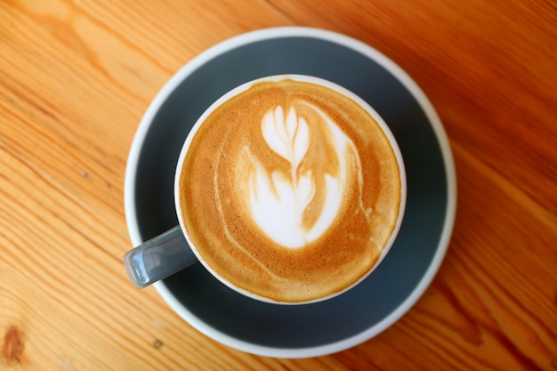 Vista superior do café cappuccino quente com latte art servido na mesa de madeira