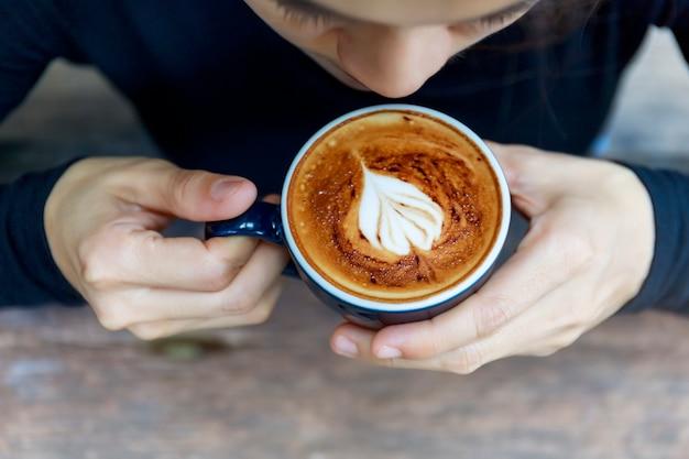 Vista superior do café cappuccino quente no café, café cremoso de forma de coração na xícara azul.