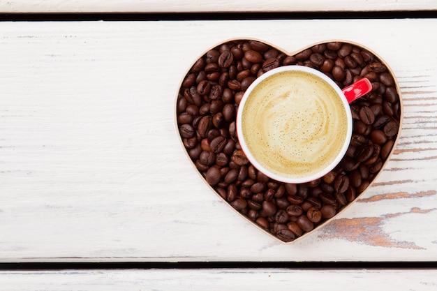 Vista superior do café com espuma cremosa. símbolo do coração de café do amor em madeira branca.