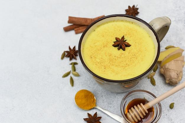Vista superior do café com leite açafrão. leite dourado em copo com anis estrelado e ingredientes ao redor. açafrão, canela, gengibre, mel, anis estrelado, cardamomo.