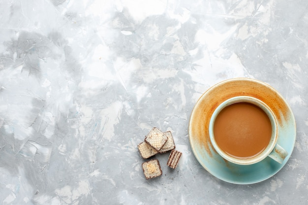 Vista superior do café com leite com waffles na mesa clara doce com açúcar waffle cor de leite