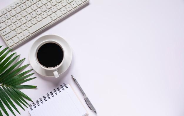 Vista superior do café com outros suprimentos e teclado em fundo branco e copie o espaço para inserir o texto.
