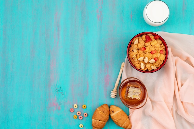 Vista superior do café da manhã com flocos de milho, frutas, leite e mel com espaço de cópia no fundo azul horizontal