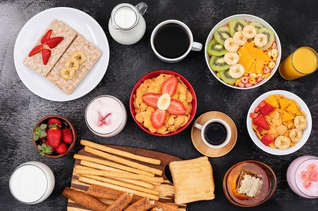 Vista superior do café da manhã com frutas, torradas, flocos de milho, iogurte na superfície preta horizontal