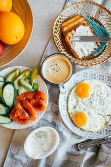 Vista superior do café da manhã com ovo, salmão, abacate, pepino, xícara de café e pão grelhado com creme de queijo. comida caseira. café da manhã da noruega.