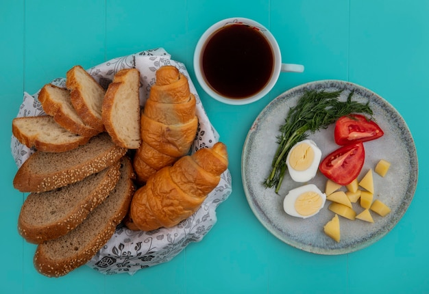 Vista superior do café da manhã com ovo, tomate, batata e endro com uma xícara de chá e pães no fundo azul