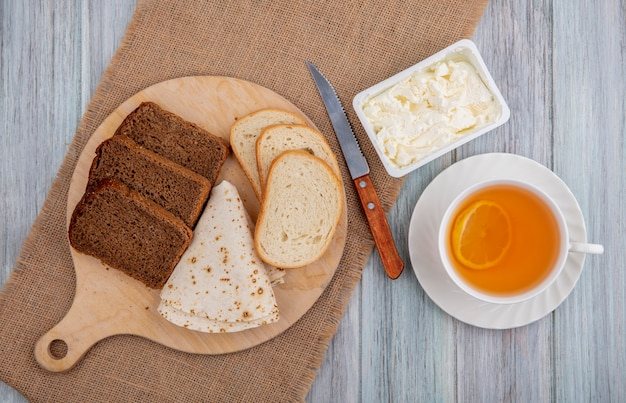 Vista superior do café da manhã com pães como fatias de centeio branco e pão achatado na tábua com faca e creme coagulado no saco e xícara de toddy quente no fundo de madeira