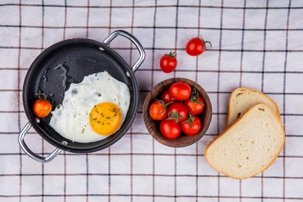 Vista superior do café da manhã com panela de ovo frito e tigela de tomate com fatias de pão em um pano xadrez