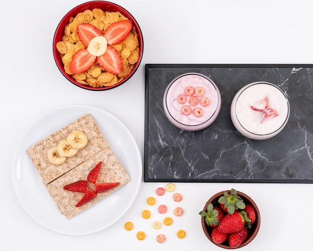 Vista superior do café da manhã com torradas, flocos de milho e iogurte na superfície branca horizontal