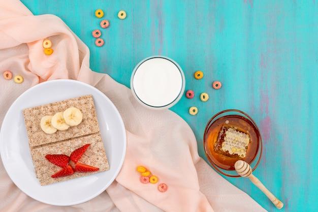 Vista superior do café da manhã com torradas, frutas, leite e mel na superfície azul horizontal