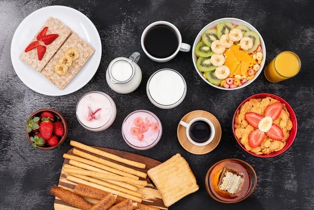 Vista superior do café da manhã com torradas, leite, flocos de milho, frutas na superfície preta horizontal