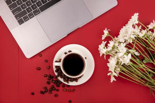 Vista superior do café em uma xícara branca com grãos de café com flores brancas em um fundo vermelho