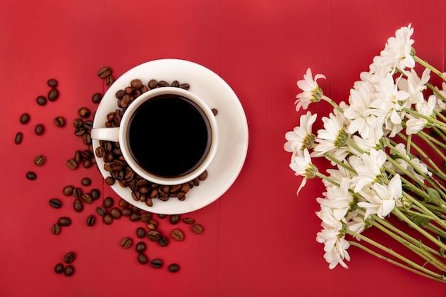 Vista superior do café em uma xícara branca com grãos de café em um fundo res