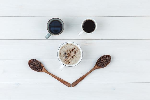Vista superior do café em xícaras com grãos de café em fundo de madeira. horizontal