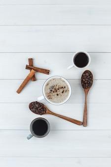 Vista superior do café em xícaras com grãos de café, paus de canela em fundo de madeira. vertical