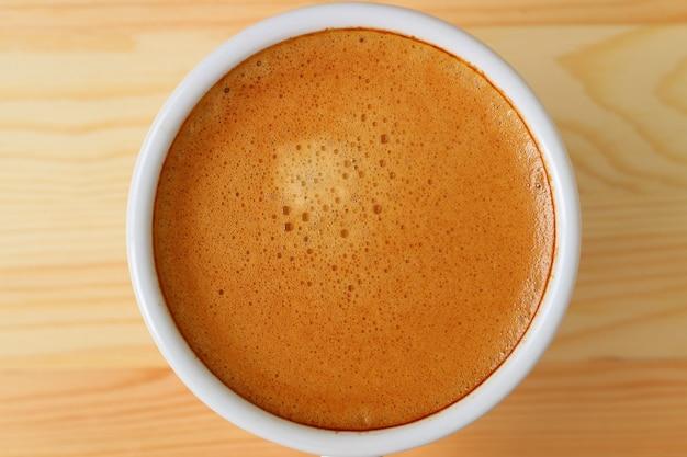 Vista superior do café expresso aromático na xícara de café branca na mesa de madeira
