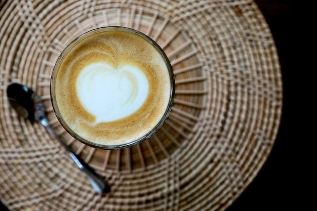 Vista superior do café fresco hot latte art em um copo com espuma de leite do coração.
