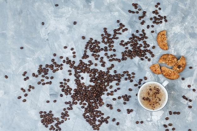 Vista superior do café na xícara com biscoitos, grãos de café em fundo cinza sujo. horizontal