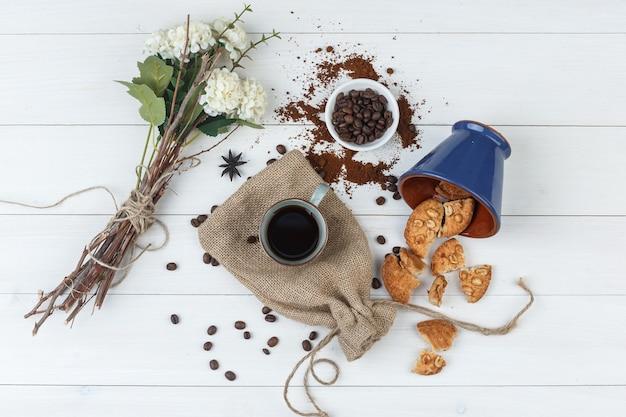 Vista superior do café na xícara com grãos de café, biscoitos, flores sobre fundo de madeira e saco.