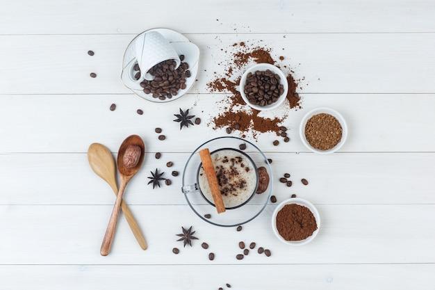 Vista superior do café na xícara com grãos de café, café moído, especiarias, tâmaras, colheres de madeira com fundo de madeira.