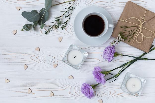 Vista superior do café, presente, velas, flores na mesa de madeira branca.
