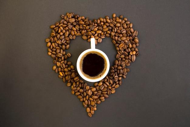Vista superior do café preto na xícara branca e coração feito de grãos de café no fundo escuro