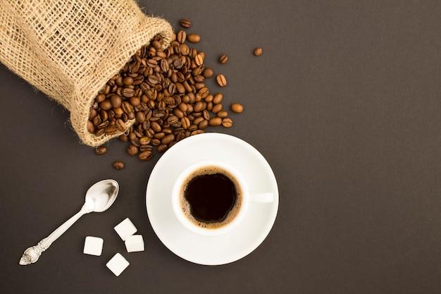 Vista superior do café preto na xícara branca e grãos de café no fundo escuro