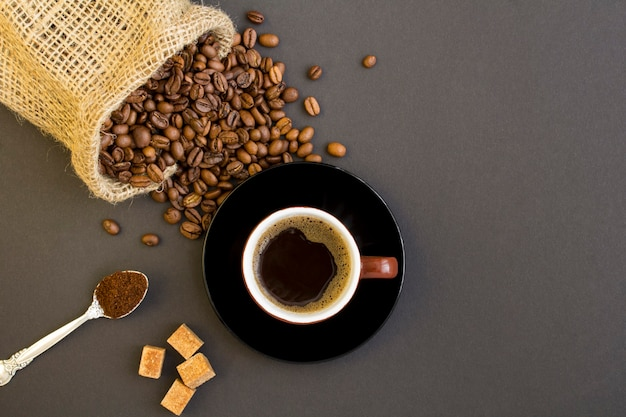 Vista superior do café preto na xícara marrom e grãos de café no fundo escuro
