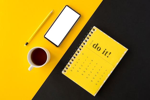Vista superior do calendário amarelo do planejador e café