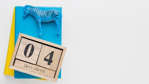 Vista superior do calendário de madeira com estatueta de zebra e livro para o dia dos animais