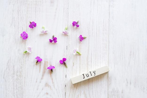 Vista superior do calendário de madeira com sighn de julho e flores cor de rosa.