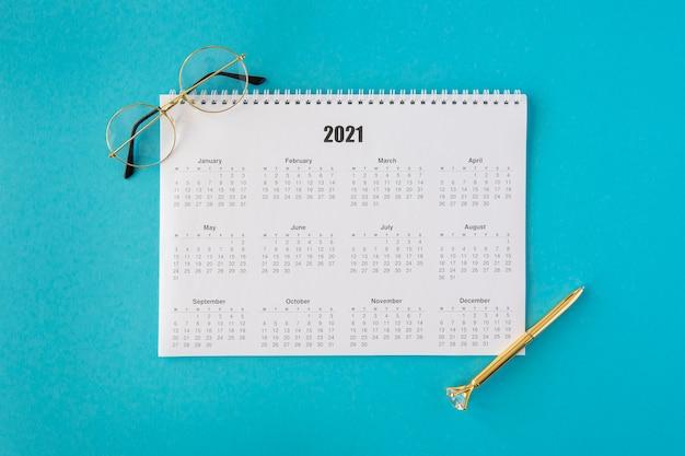 Vista superior do calendário de papelaria com óculos de leitura