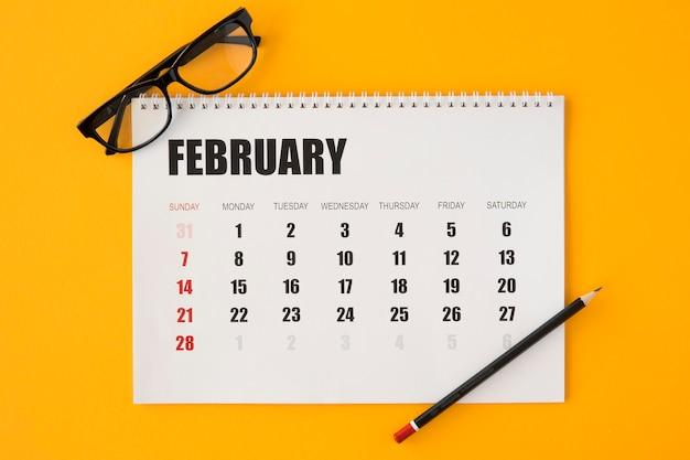 Vista superior do calendário de papelaria em fundo amarelo