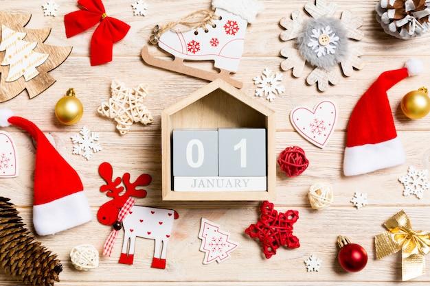 Vista superior do calendário na mesa de madeira de natal. o primeiro de janeiro. brinquedos e decorações de ano novo. conceito de férias