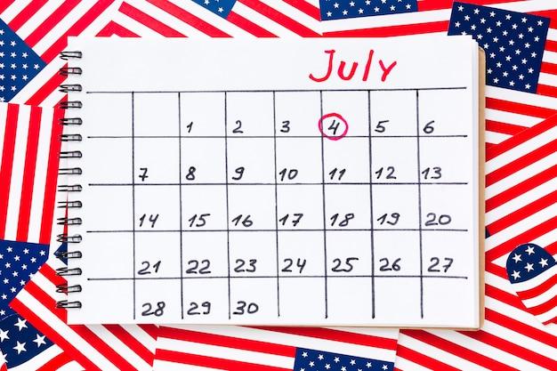 Vista superior do calendário para o mês de julho com bandeiras americanas