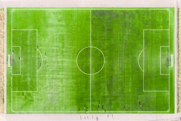 Vista superior do campo de futebol, campo de futebol. vista aérea do campo de futebol real. jogadores de futebol jogam no gramado aparado do estádio.
