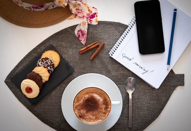 Vista superior do canto do café da manhã com uma xícara de cappuccino com espuma de leite e cacau em pó e biscoitos redondos em uma mesa branca - smartphone e bloco de notas