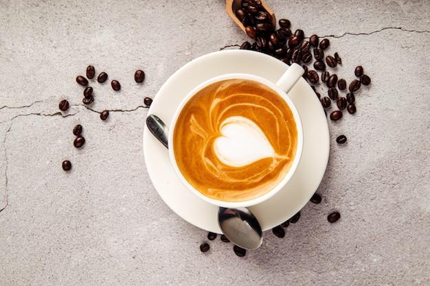Vista superior do cappuccino decorado com café em uma xícara branca no fundo de concreto