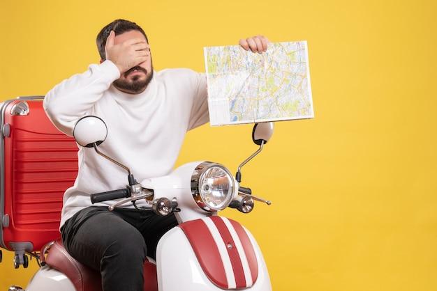 Vista superior do cara emocional sentado na motocicleta com a mala segurando o mapa no fundo amarelo isolado