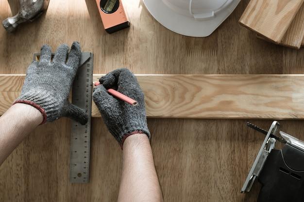Vista superior do carpinteiro medir e escrever na madeira