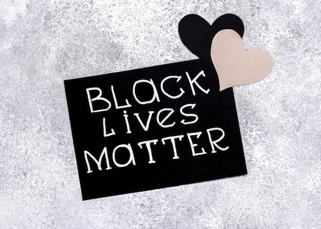 Vista superior do cartão com matéria de vidas negras e corações