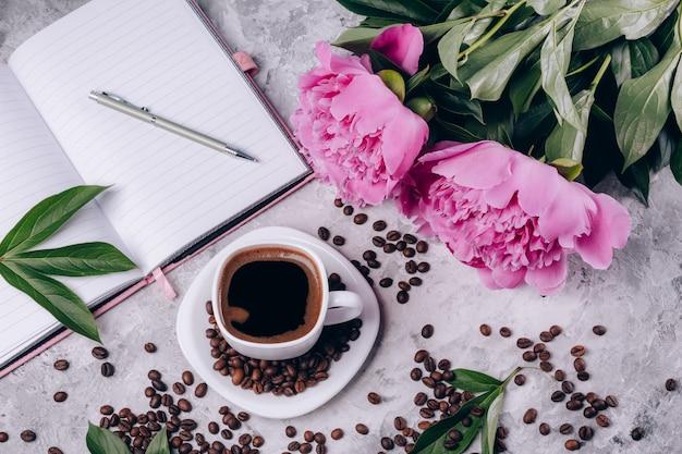 Vista superior do cartão de café em uma xícara ao lado de peônias e um notebook em um concreto cinza brilhante