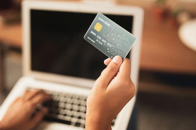 Vista superior do cartão de crédito realizada na mão com laptop turva em segundo plano