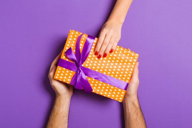 Vista superior do casal dando e recebendo um presente em fundo colorido. conceito romântico com espaço de cópia