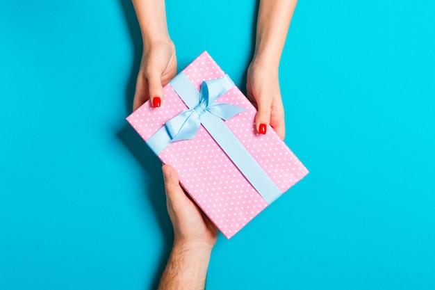 Vista superior do casal dando e recebendo um presente. feche acima do conceito romântico
