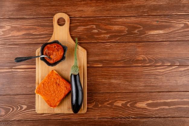 Vista superior do caviar de berinjela em pires e torradas com legumes caviar berinjela madura fresca na placa de madeira no fundo rústico, com espaço de cópia